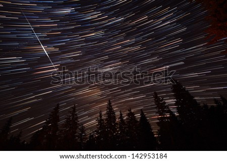 Colorful star trails with pine forest and meteorite strike - stock photo