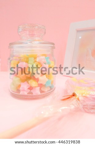 Colorful stars candy in a jar, with blur lollipop and picture frame on the side. On pink wallpaper background. Girly interior decoration