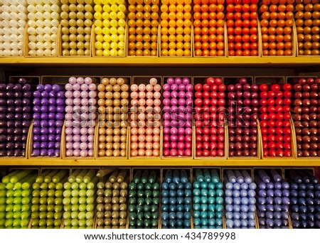 Colorful stick candles arranged in shelves and sorted by color in a candle shop. - stock photo