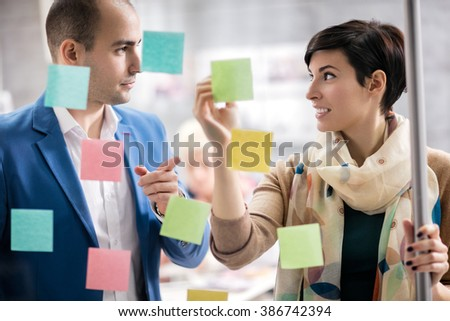 Colorful stickers on glass panel help female designer and her associate in job - stock photo