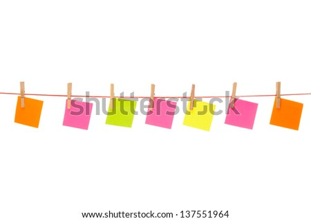 Colorful stickies hanged on red rope isolated on white