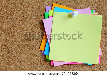 colorful sticky notes on cork bulletin board - stock photo