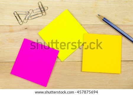 Colorful sticky notes with clips and pen on wood background