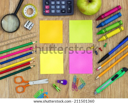 Colorful sticky notes with school items over wooden background  - stock photo