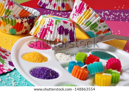Colorful still life of cupcake supplies with an artist's theme - includes wrappers with splattered paint design and palette filled with sugar sprinkles and candles.