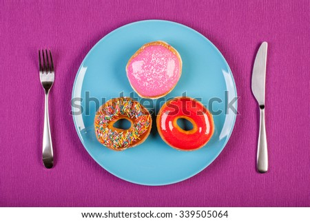 colorful stock image of doughnuts on a plate. diet conceptual - stock photo