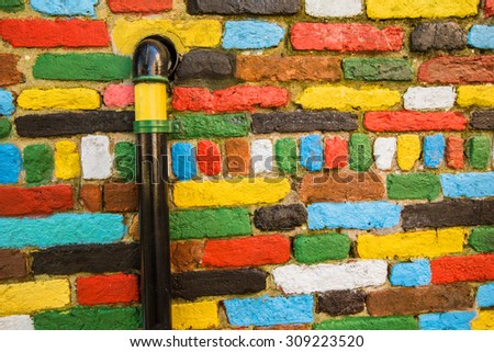 Colorful stone brick wall with painted pipilne on left side of picture