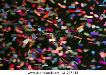 Colorful streamers on black background - stock photo