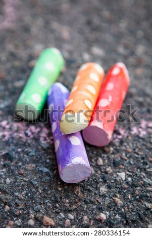 Colorful street chalk on asphalt - stock photo