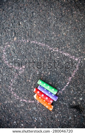Colorful street chalk outdoors on asphalt with a heart drawn to the ground - stock photo