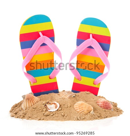 Colorful striped flip flops at the summer beach - stock photo