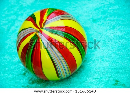 Colorful striped glass marble ball isolated on turquoise velvet background.