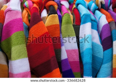 Colorful striped pullovers on hangers. - stock photo