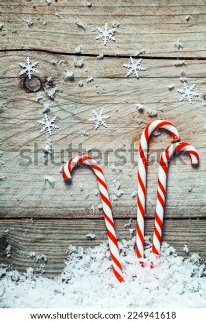 Colorful striped red and white Xmas candy canes with scattered winter snow lying on old cracked dried wooden boards with copyspace - stock photo
