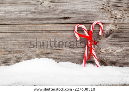 Colorful striped red and white Xmas candy canes with winter snow on wooden boards, with copyspace - stock photo