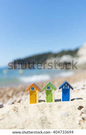 Colorful striped wooden beach cabins at the coast - stock photo