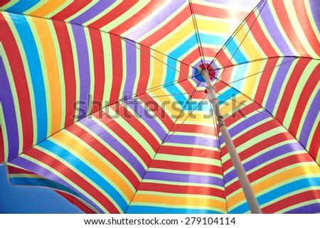 colorful stripes beach umbrella on blue sky - stock photo