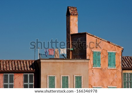 Colorful stucco buildings with laundry, television antenna, windows  and  shutters