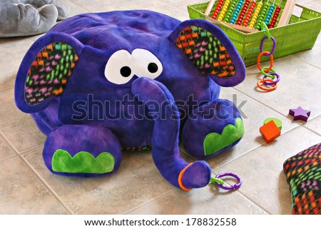 Colorful stuffed elephant with pillow and basket of toys on tile in kids playroom.  (Elephant is a handcrafted beanbag floor pillow made of fleece fabric) - stock photo
