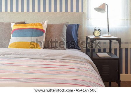 Colorful style bedding bedroom interior and clock on bedside table - stock photo