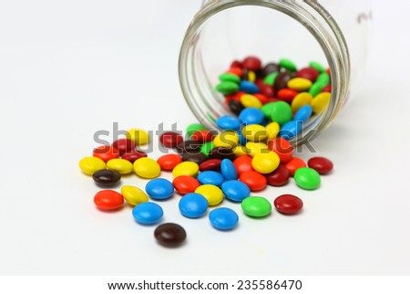 Colorful sugar-coated chocolate smarties in a glass jar on a white background