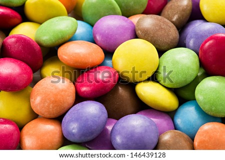Colorful sugar-coated chocolate smarties in the colors of the rainbow or spectrum - stock photo