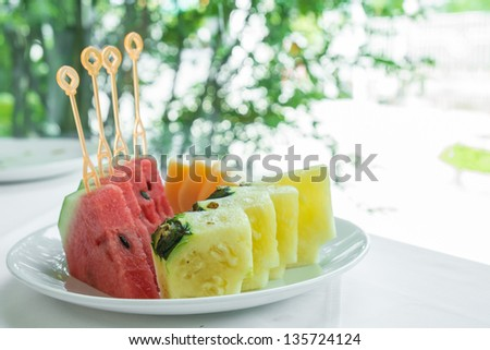 Colorful summer fruit platter with pineapple, watermelon on white table in restaurant - stock photo