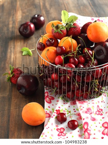 Colorful summer fruit  with sweet cherries, apricots, strawberries and plums - stock photo
