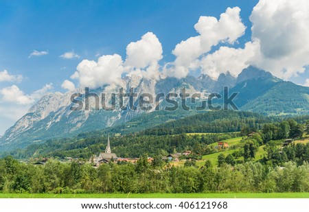 Colorful summer landscape of big clouds over the rocky wild mountains and small village of the austrian Alps, near Salzburg, Austria - stock photo