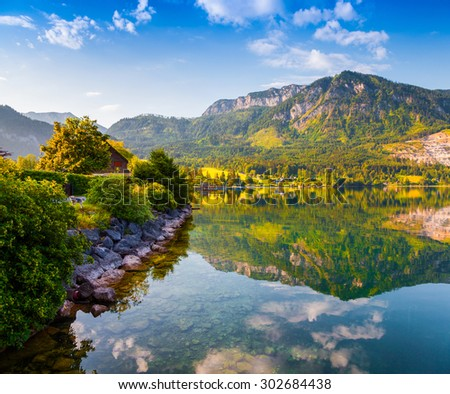 Colorful summer morning on the Grundlsee. Gossl village in the morning mist. Alps, Austria, Europe.