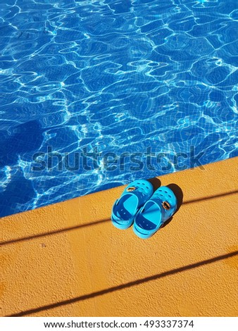 colorful summer photo, baby and children clogs on the water pool