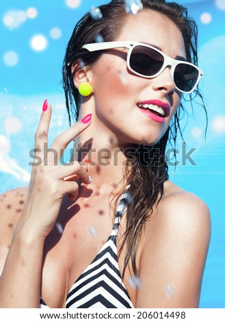 Colorful summer portrait of young attractive happy brunette woman wearing sunglasses at the swimming pool  - stock photo