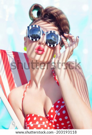 Colorful summer portrait of young attractive woman wearing bikini and sunglasses sitting by the swimming pool - stock photo