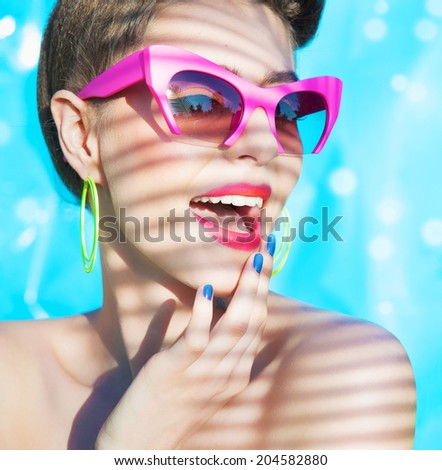 Colorful summer portrait of young attractive woman wearing  sunglasses under a palm tree by the swimming pool  - stock photo