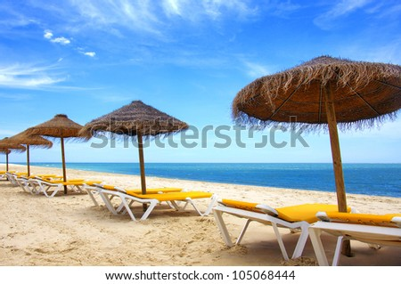 Colorful summer scene with sun-shades and deck-chairs in a beach with golden sand