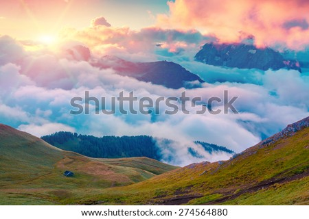 Colorful summer sunrise in the foggy Val di Fassa valley with passo Sella . National Park. Dolomites, South Tyrol. Location Canazei, Campitello, Mazzin. Italy, Europe.  - stock photo