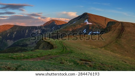 Colorful summer sunset in the Carpathian mountains with road and green grass. Svidovets ridge, Ukraine, Europe.