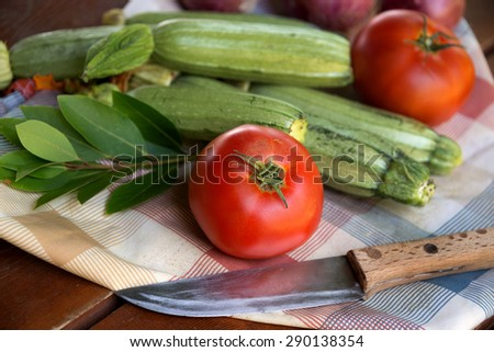 Colorful summer vegetables tomatoes, zucchini and onions on a rustic wooden background.