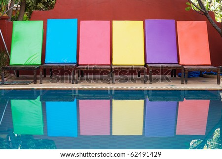 Colorful sun loungers in a row next to a swimming pool - stock photo