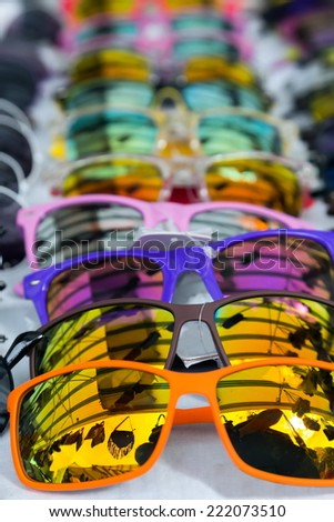 colorful sunglasses lying in a line on a table
