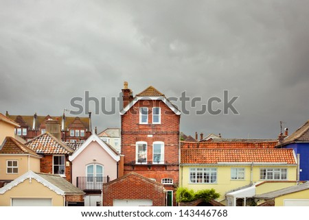 Colorful sunlit buildings in Aldgeburgh, Suffolk, on a stormy day