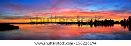 Colorful sunrise over a still lake in the early morning - stock photo