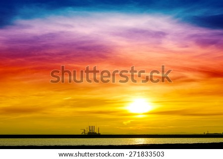 Colorful sunrise over industrial infrastructure in Swinoujscie harbor, Poland.
