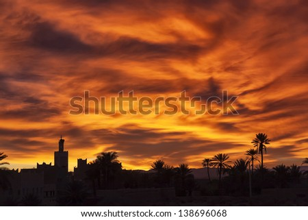 Colorful sunrise with mosque and date palms in Ouarzazate, Morocco. - stock photo