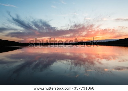 Colorful sunset and reflection at small lake - stock photo