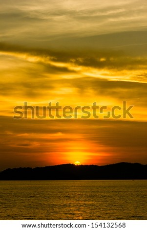 Colorful sunset behind a tropical island - stock photo