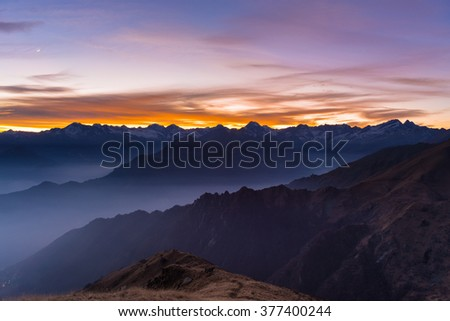 Colorful sunset behind majestic mountain peaks of the Italian Alps. Fog and mist covering the valleys below, autumnal landscape, cold feeling. Stunning sky with half moon. - stock photo