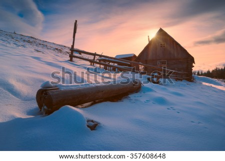 Colorful sunset in a Carpathian village. Winter snow-capped valley with rustic wooden houses - stock photo