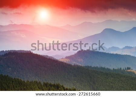 Colorful sunset in the mountains landscape. Dramatic overcast sky. Filtered image:cross processed vintage effect.  - stock photo