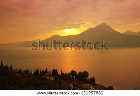 colorful sunset landscape at garda lake, italy - stock photo